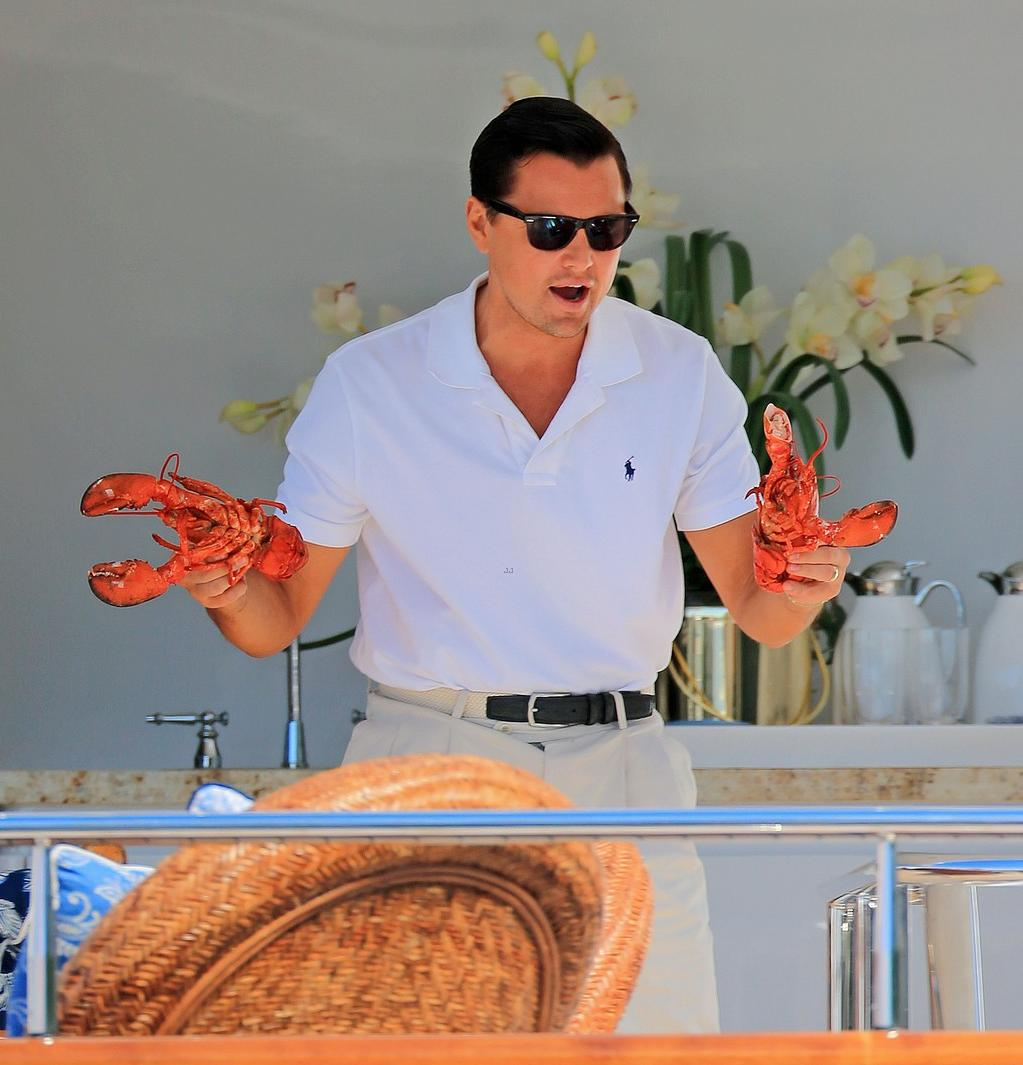 Leonardo DiCaprio plays around with one lobsters in each hand on the set of 'Wolf of Wall St.' on a yacht in NYC